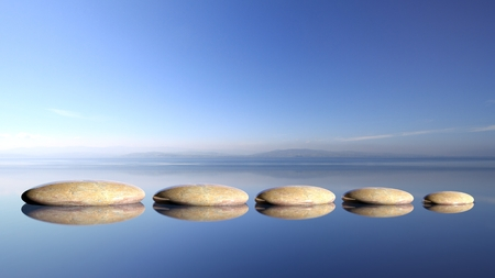 Photo pour Zen stones row from large to small  in water with blue sky and peaceful landscape background. - image libre de droit