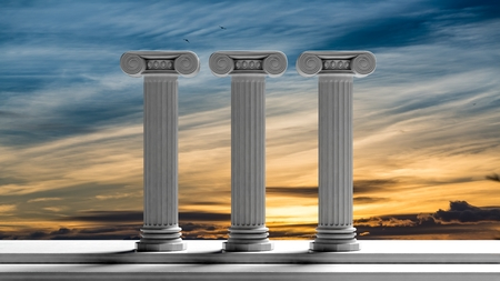 Three ancient pillars with sunset sky background.