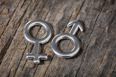 Closeup of two metallic gender symbols, on wooden background.