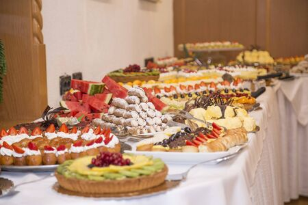 Photo pour buffet with sweets. fruits and other sweets on dessert table. Rows of tasty looking desserts in beautiful arrangements. Sweets on banquet table - picture taken during catering event - image libre de droit