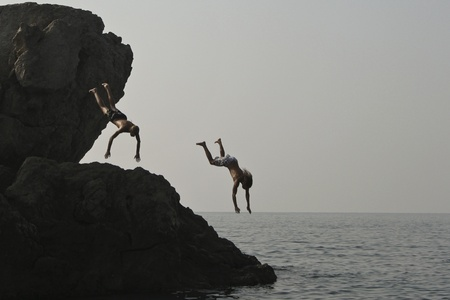 Alupka, Ukraine - August, 18, 2010. Two unidentified young men jumped into the sea from a cliff. The action took place in Alupka on the beach