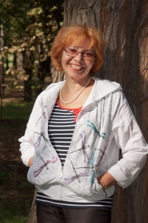 Middle-aged woman in glasses smiling near big tree