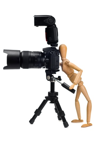 The wooden figure of photographer who photographed SLR camera on a tripod isolated on a white background
