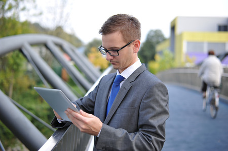 Businessman using computer tablet, Shot in the city, late afternoon early evening  Man is wearing a gray suit and blue tie