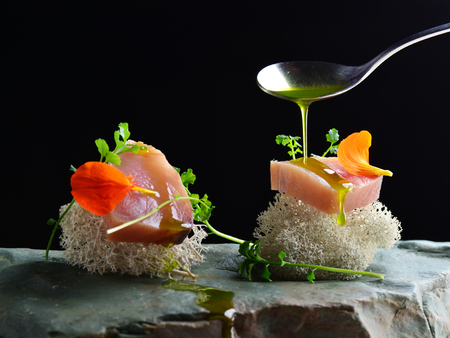 Photo for Fine dining, fresh raw ahi tuna sashimi served on sponge with herbs - Royalty Free Image