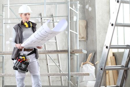 Photo pour woman construction worker builder looking at bluprint, wearing helmet, hearing protection headphones and tools belt bag in building site indoors background. - image libre de droit