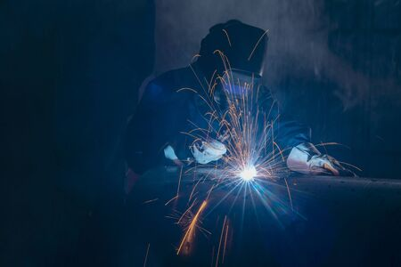 Photo pour Professional welder and mask welding metal pipe on the industrial table. - image libre de droit