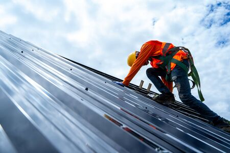 Photo pour Roofer working on roof structure of building on construction site,Roofer using air or pneumatic nail gun and installing Metal Sheet on top new roof. - image libre de droit