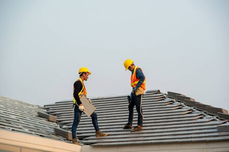Photo pour Construction worker wearing safety harness belt during working on roof structure of building on construction site,Roofer using air or pneumatic nail gun and installing concrete roof tile on top new roof. - image libre de droit