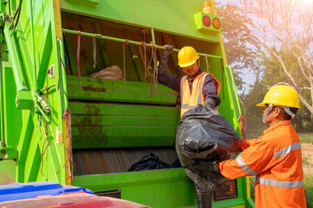 Photo pour Two garbage men working together on emptying dustbins for trash removal with truck loading waste and trash bin. - image libre de droit