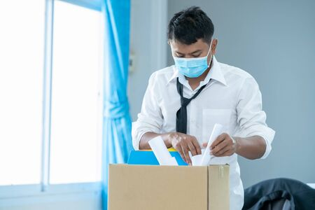Photo for Unemployed man,Businessman has a brown cardboard box and resignation letter write reason for resigning from work from the COVID 19 disease situation,Coronavirus has turned into a global emergency. - Royalty Free Image