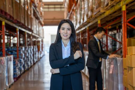 Photo pour Portrait of business women with crossed arms standing in a large warehouse. - image libre de droit