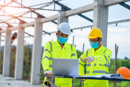 Photo for Two engineers wearing protective mask to Protect Against Covid-19 and checking production process in building construction site,Construction,Building, teamwork and people concept. - Royalty Free Image