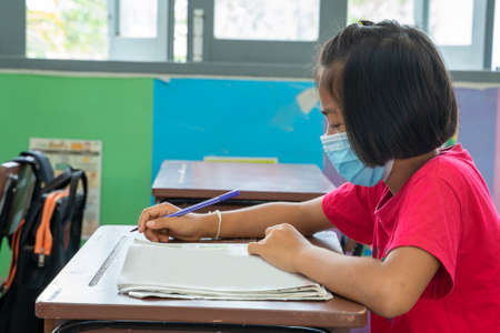 Photo pour Asian elementary school wear mask for protect corona virus desk trying to find new ideas for schoolwork,Education,Elementary school, Learning and people concept. - image libre de droit