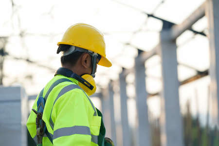 Photo pour Engineer technician wearing safety harness and safety line working at construction site. - image libre de droit