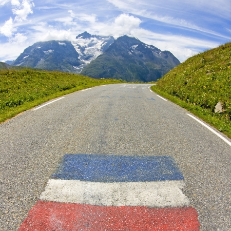 Road in mountain, french alps with french flag.