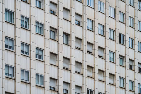 Photo pour Rows of windows with roller shutters on the facade of an urban building - image libre de droit