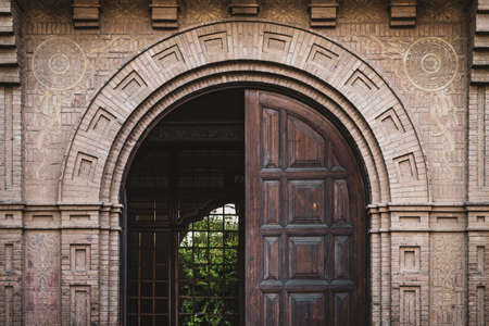 Photo pour Front view of a half-opened wooden door from an industrial building - image libre de droit