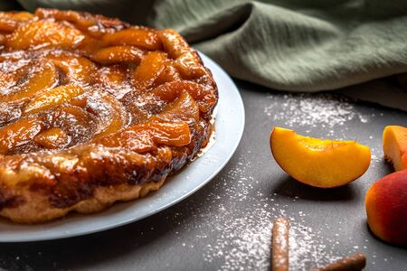 Photo for Tarte Tatin with peaches, caramel and powdered sugar close-up on a white plate on a dark background with a linen napkin. Near slices of peach and cinnamon sticks. Horizontal orientation - Royalty Free Image