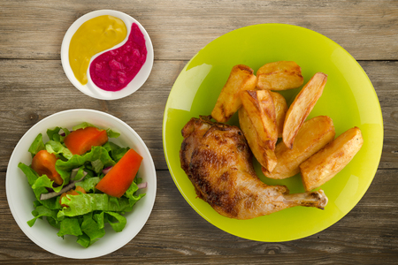 Chicken thigh with French fries on a wooden background. chicken thigh on a plate. rustic food