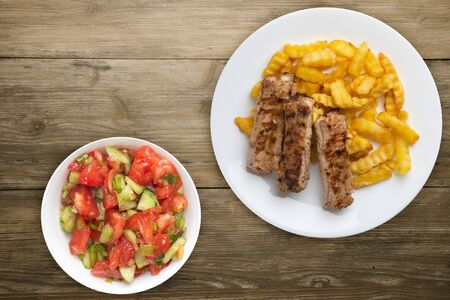 Photo pour pork ribs and potatoes on a white plate with vegetable salad and sauce on a wooden background. Top view of fast food. unhealthy food.flat lay - image libre de droit