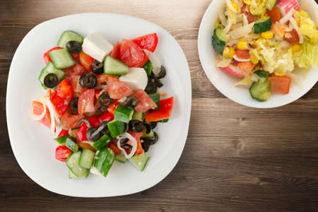 Photo pour Greek salad on brown wooden background. Greek salad on white plate with vegetarian salad top view. healthy food - image libre de droit