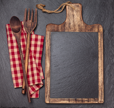 Cutting board, tablecloth, wooden spoons and piece of chalk. Over dark slate board.