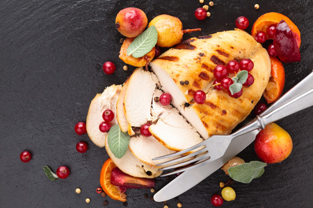Closeup shot of baked chicken breast with sage and baked fruits on slate.