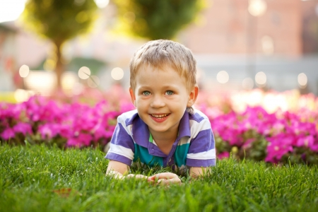 Portrait of adorable little boy among the flowers. Summer holiday.