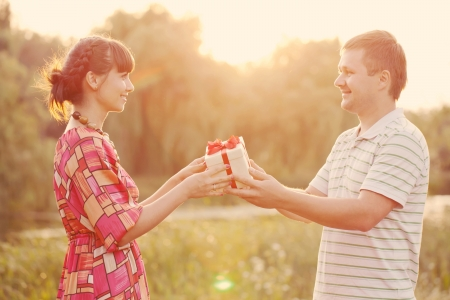 Man giving to his woman a gift box. Happy middle-aged couple in love outdoors in the sunlight at sunset. Happy family concept. Retro style.