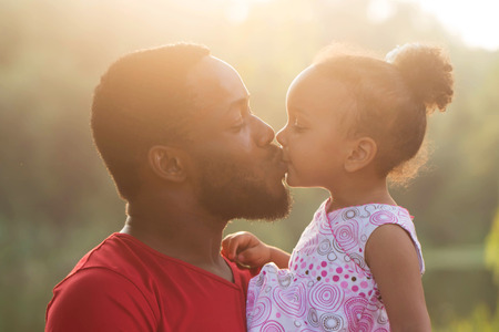 Foto de Black father kissing baby daughter at sunset. Happy family concept. - Imagen libre de derechos