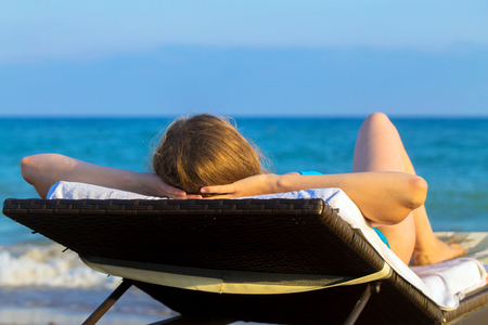 Young blonde woman takes sunbathing on lounger on the beach near the sea. Summer holidays concept.