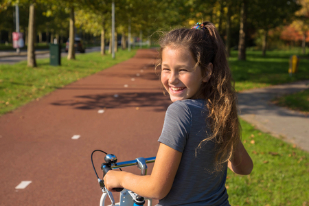 Foto de Happy child rides a bike on bike path. Cyclist child or teenager girl enjoys good weather and cycling. Environmentally friendly transport concept. Girl is smiling and laughs. Netherlands, Holland. - Imagen libre de derechos
