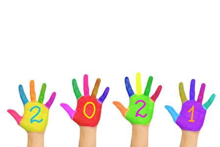Foto de The number 2021 written on the brightly painted hands. New Year and holiday concept. Colorful palms, people are celebrating holidays. Isolated on a white background. - Imagen libre de derechos