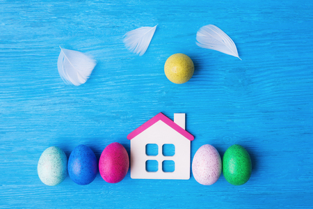 Photo for Easter concept with decorative eggs, toy house and feathers as clouds on blue - Royalty Free Image