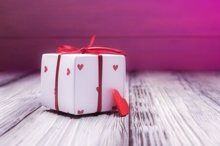 Foto de Gift box and red heart over pink blur background. Valentines day concept - Imagen libre de derechos