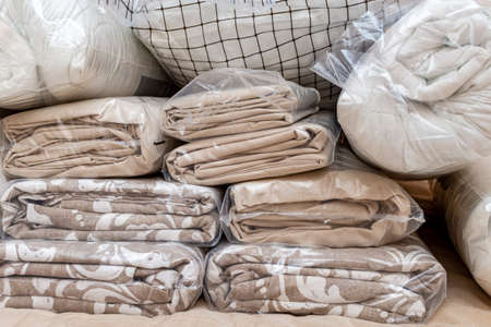 White and beige packed pile of the linen bedclothes blanket with pillow and bedding sheets