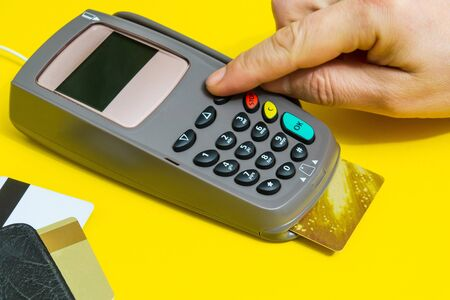 Photo pour Hand entering pin code to money terminal before payment on yellow background - image libre de droit