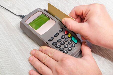 Photo pour Hand inserts bank card into money terminal for payment on desk top view - image libre de droit