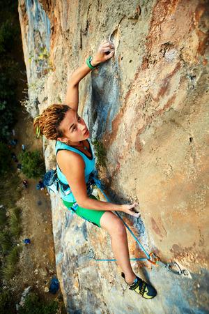Photo pour female rock climber climbs on a rocky wall - image libre de droit