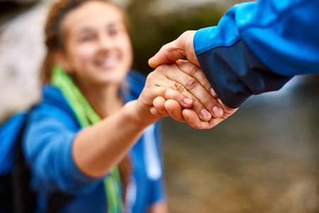 Photo for Helping hand - hiker woman getting help on hike smiling happy overcoming obstacle. Tourist backpackers walking in autumn forest. Young couple traveling. - Royalty Free Image