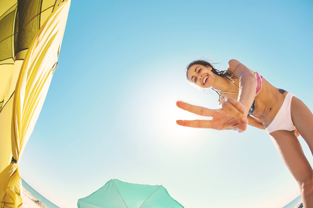 beautiful smiling woman looks inside the tent and shows Victory sign in camera . view from inside tent on the sea and sandy beach with beach umbrella and beach chair on a bright sunny day. young couple having a vacation at sea.
