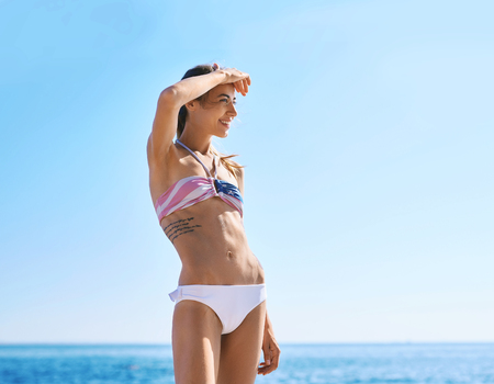 Photo pour Portrait of young beautiful woman with fit body in white bikini against blue sky and sea on the beach. Slim pretty model in swimwear posing, sunbathing on the sea shore, is protected by hand from the sun. Summer vacation and tanning concept. - image libre de droit