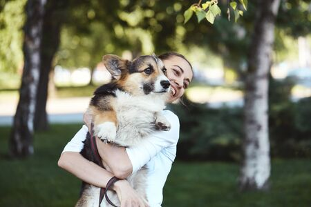Photo pour Welsh Corgi Pembroke dog and smiling happy woman together in a park outdoors. Young female in white shirt playing, embracing, holding a her cute pet. Focus on the Corgi dog. Concept friendship with dog and human, cute moments, happines. - image libre de droit