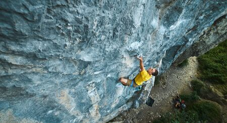 Foto de top view of man rock climber in yellow t-shirt, climbing on a cliff, searching, reaching and gripping hold. Conquering, overcoming and active lifestyle concept. - Imagen libre de derechos