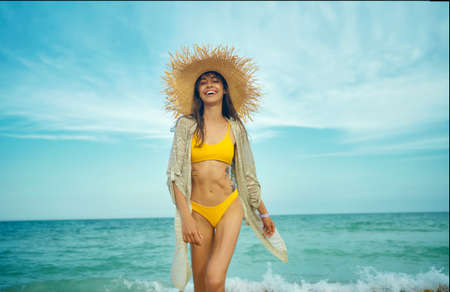 Photo for Joyful happy travelr woman in fashionable swimwear and straw hat goes on camera wiht sea view on background. tourism and sea resort, latin woman on vacation - Royalty Free Image