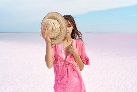 Photo pour sensual portrait elegant fashion woman in pink dress on paradise landscape of salt flats on pink lake with copy space, model covering half face with hat. focus on hat - image libre de droit