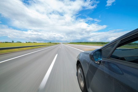 The car moves at great speed on highway at the sunny summer day.