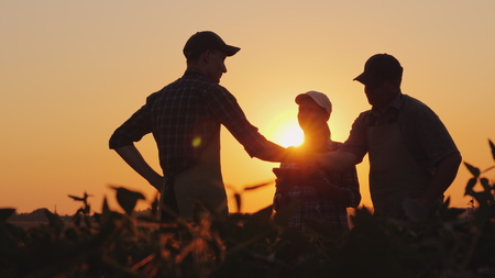 Photo pour A group of farmers in the field, shaking hands. Family Agribusiness - image libre de droit