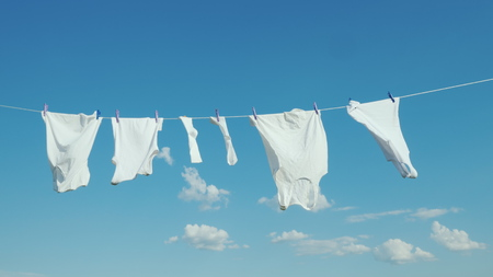 Photo pour White linen dries on the rope against the blue sky - image libre de droit